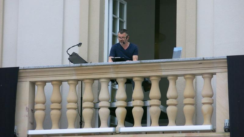 """Jacek Braciak interpretuje fragment """"Procesu"""" Franza Kafki na patio budynku A-1 Politechniki Wrocławskiej, fot. Bartosz Moch"""