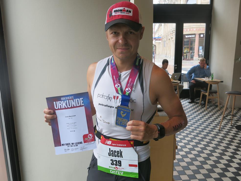 Jacek Marciniak z medalem i certyfikatem ukończenia wyścigu
